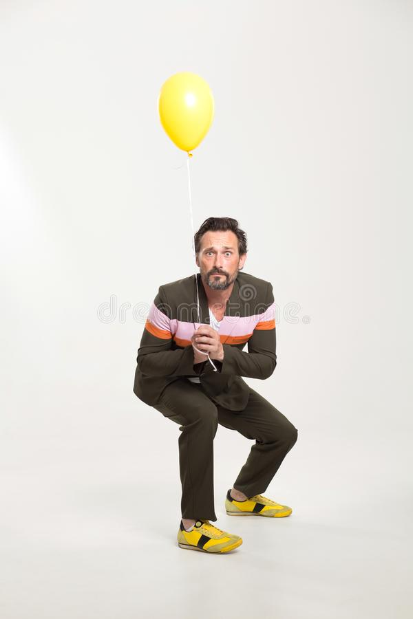 Happy man with yellow balloon. Man in black suit on white background. Holding yellow balloon stock image