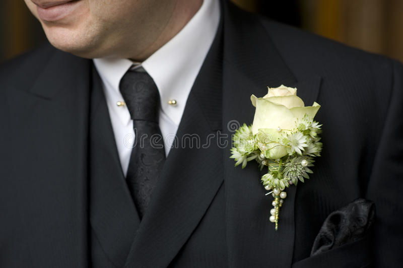 Man in black suit with white rose buttonhole