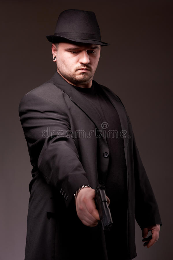 Man In Black Suite With Gun. Stock Photo