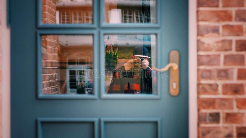 Man in Black Sweater Taking Photo of Blue Door stock image