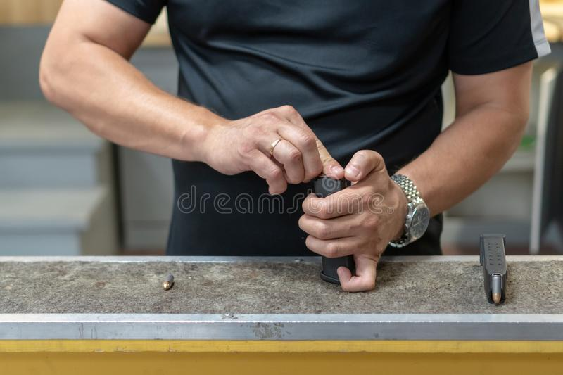 A man in a black T-shirt charges the pistol holder with 9 19 cartridges.  stock images