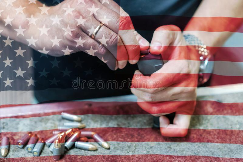 A man in a black T-shirt charges the pistol holder with 9 19 cartridges against the background of the American flag.  royalty free stock images