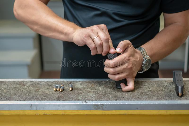 A man in a black T-shirt charges the pistol holder with 9 19 cartridges. A man in a black T-shirt charges the pistol holder with 9 19 cartridges royalty free stock photography