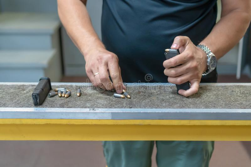 A man in a black T-shirt charges the pistol holder with 9 19 cartridges. man`s hands loading a pistol magazine. man loads the cli. P of pistol royalty free stock photos