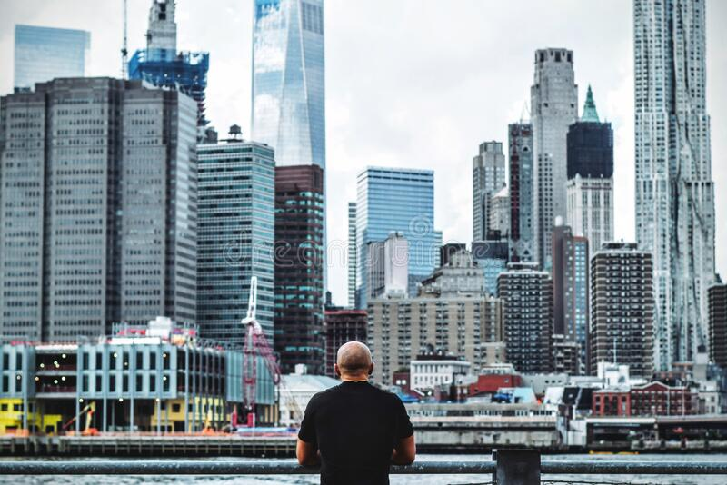 Man in Black T Shirt in Front on City Skyline during Daytime royalty free stock photography