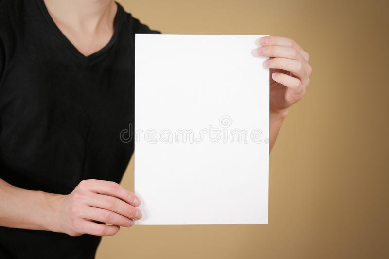 Man in black t shirt holding blank white A4 paper. Leaflet presentation. Pamphlet hold hands. Man show clear offset paper. Sheet royalty free stock photography
