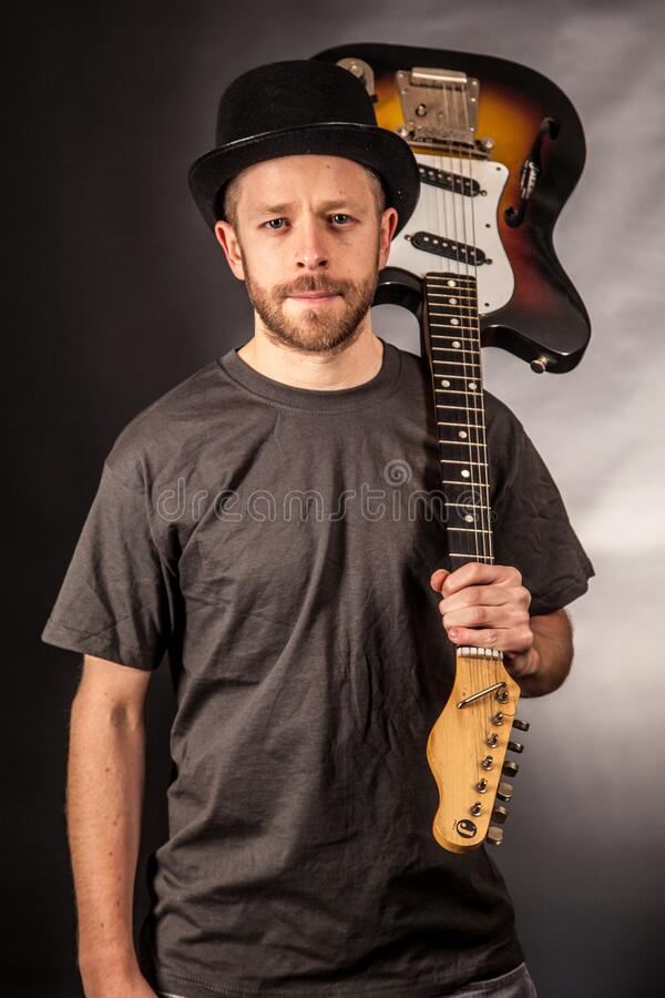 Man In Black T Shirt Holding Electric Guitar Upside Down Free Public Domain Cc0 Image