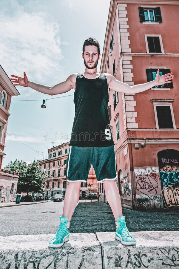 Man In Black Tank Top And Green Shorts Posing Near Building royalty free stock image