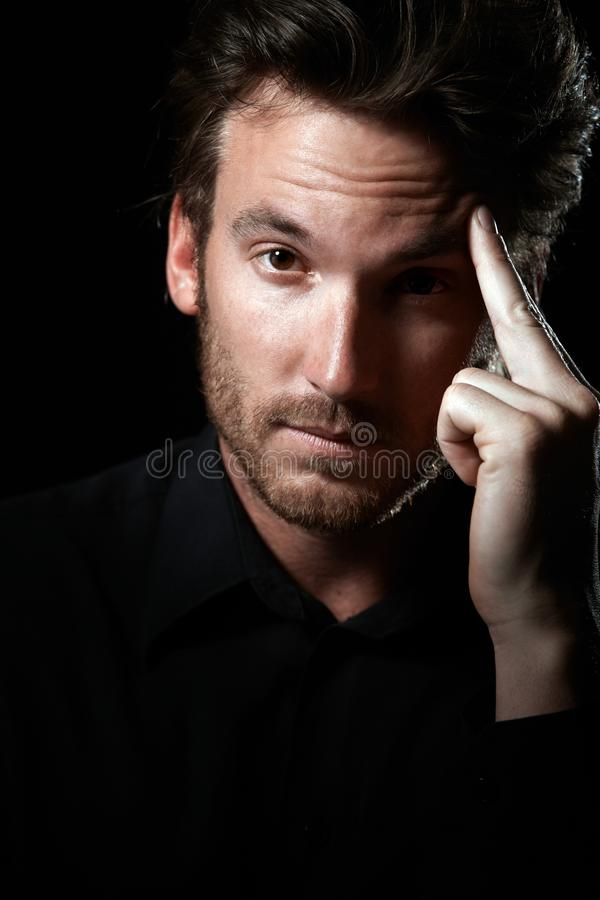 Man in black thinking stock image