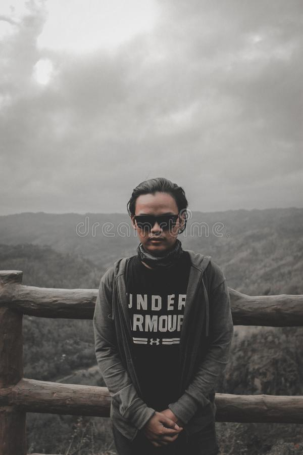 Man in Black Top and Grey Hoodie Jacket Standing Beside Brown Wooden stock photography