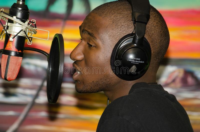 Man in Black Tops Wearing Black Headphones Singing in Front of Black Condenser Microphone stock photo