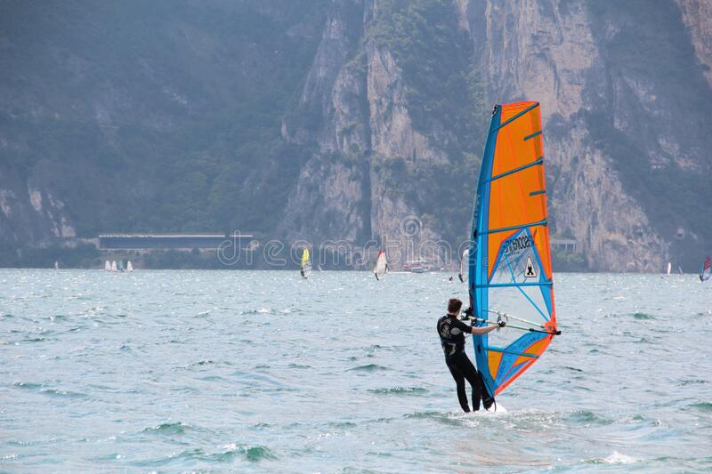 Man In Black Wetsuit Standing On Orange And Blue Sailboat During Daytime Free Public Domain Cc0 Image