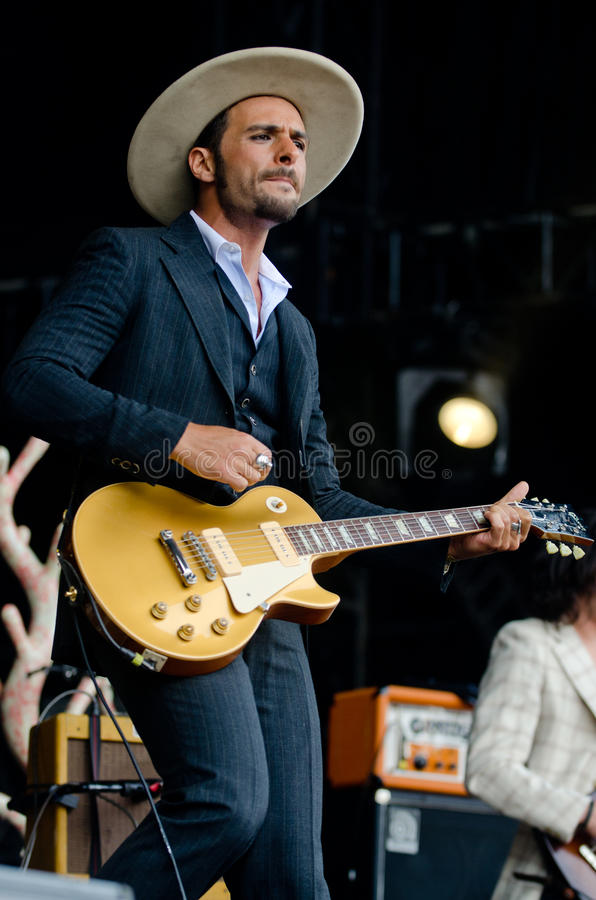 Man in Black and White Pinstripe Formal Coat and Pants Wearing Beige Hat Holding Brown Electric Guitar royalty free stock photo