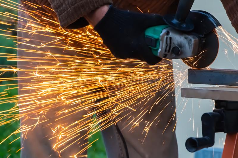 A man in the black working gloves cuts metal using an angle grinder tool with beautiful yellow sparks on a work bench stock image