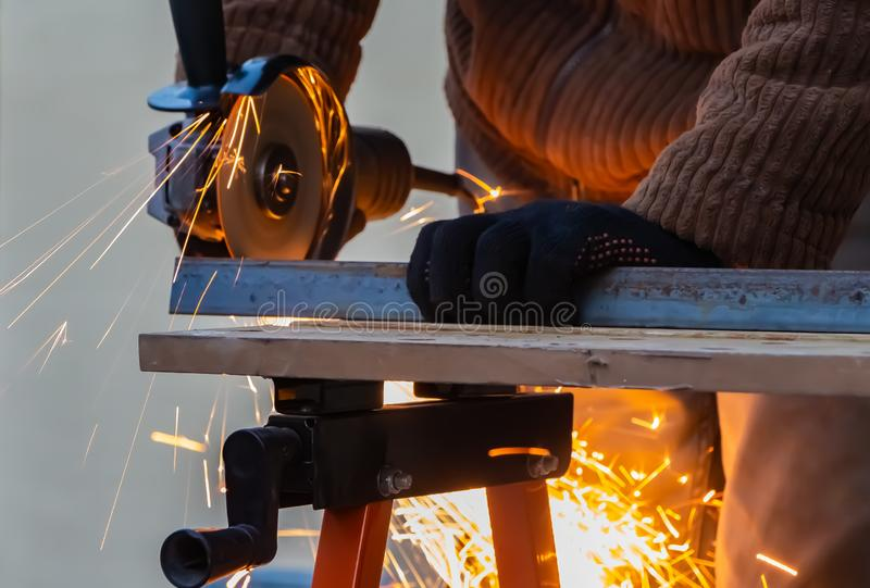 A man in the black working gloves cuts metal using an angle grinder tool with beautiful yellow sparks on a work bench stock photography