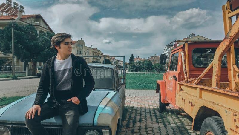 Man In Black Zip-up Jacket On Blue Car Beside Orange Truck stock image