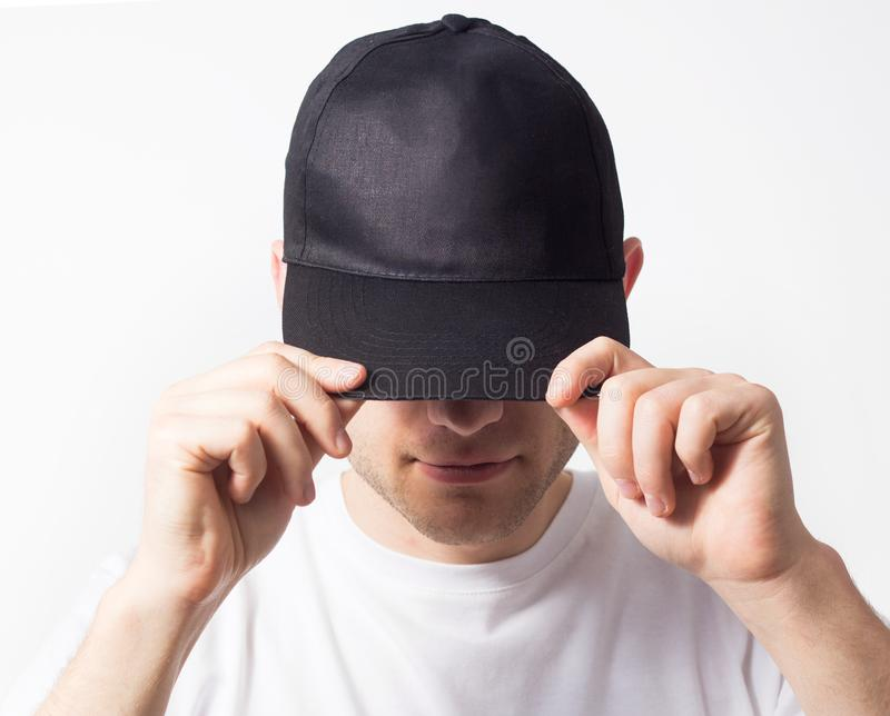 The man, in the blank black, baseball cap, snapback on a white background, mock up, free space, logo presentation. The man, in the blank black, baseball cap stock photo