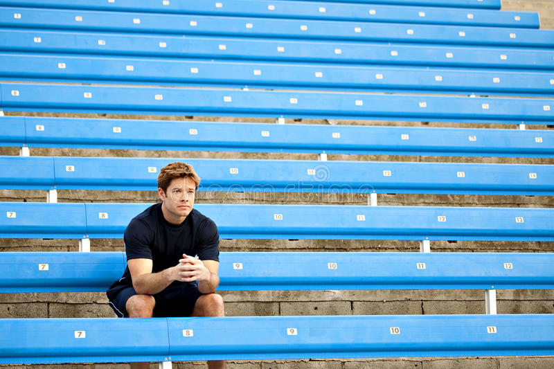 Man bleachers. Male athlete sitting in the bleachers stock photography