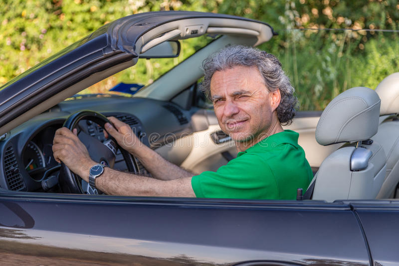 Man blinded by the light while driving. A convertible car is uneasily smiling royalty free stock photos
