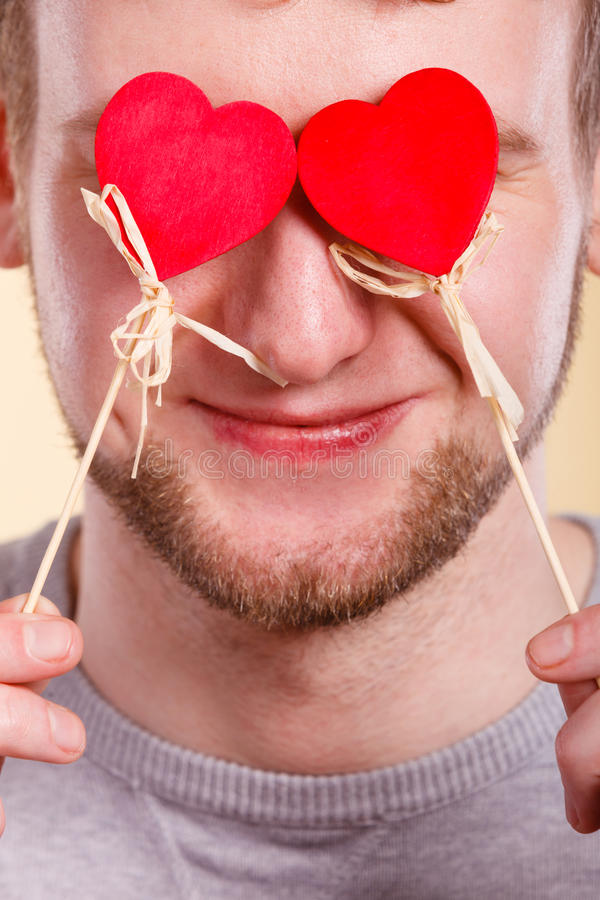 Man blinded by love. Love romance concept. Man blinded by love. Young male holding hearts on sticks before his eyes royalty free stock photos