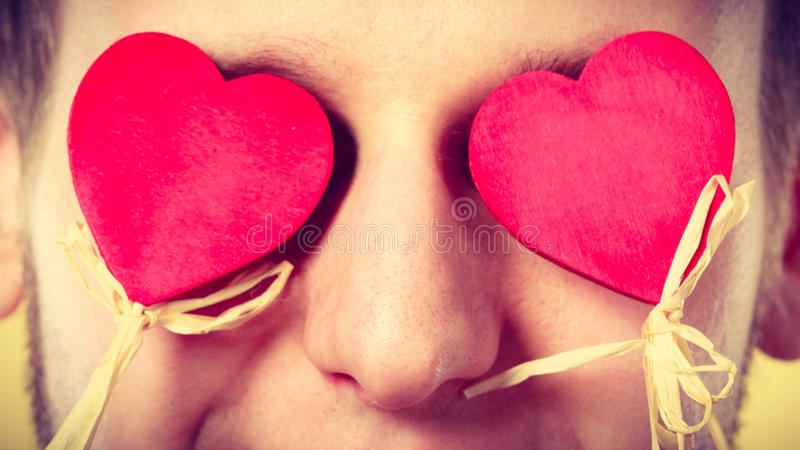 Man blinded by love. Love romance concept. Man blinded by love. Young male holding hearts on sticks before his eyes royalty free stock images