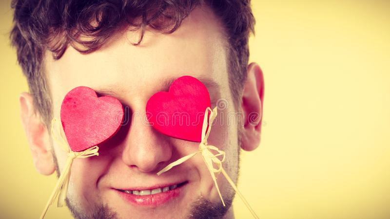 Man blinded by love. Romance feelings valentines present concept. Man blinded by love. Young male covering his eyes with hearts stock image