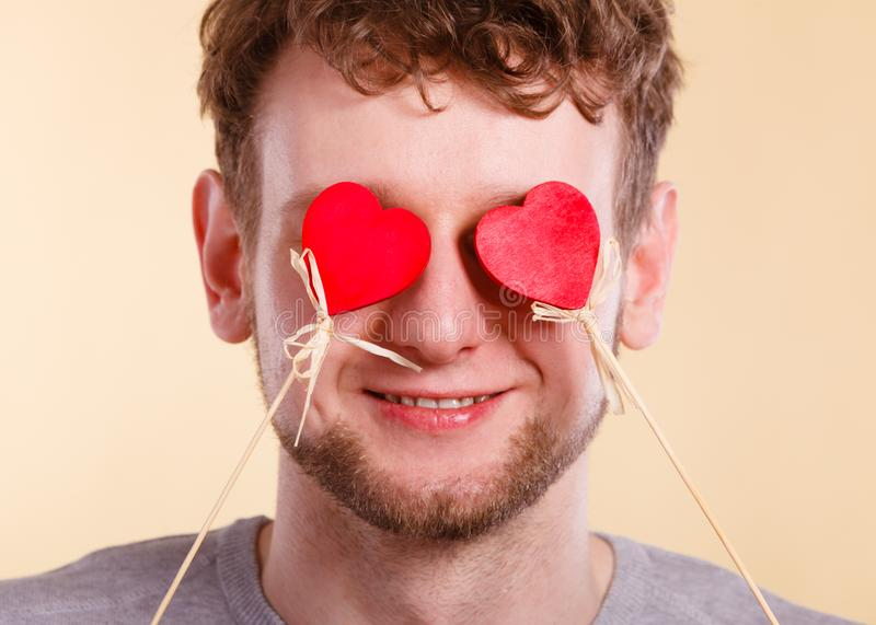 Man blinded by love. Romance feelings valentines present concept. Man blinded by love. Young male covering his eyes with hearts royalty free stock photo