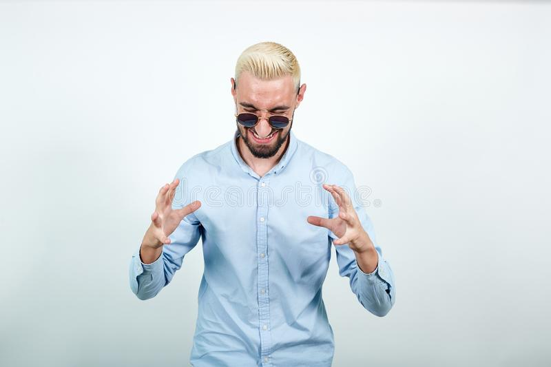 Man with blond hair, black beard over isolated white background shows emotions stock photo