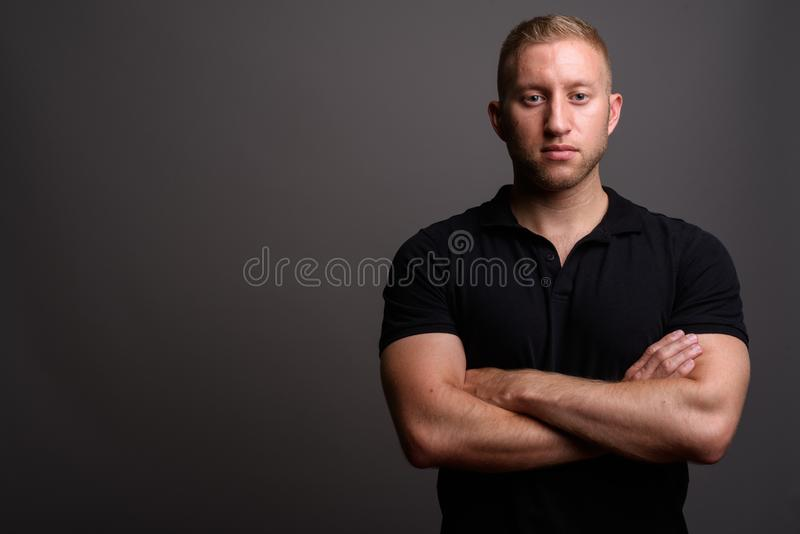 Man with blond hair wearing black polo shirt against gray backgr. Studio shot of man with blond hair wearing black polo shirt against gray background stock photos