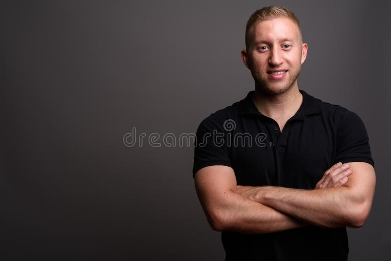 Man with blond hair wearing black polo shirt against gray backgr stock photos