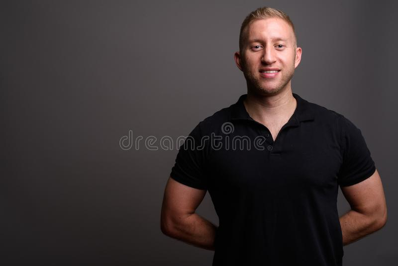 Man with blond hair wearing black polo shirt against gray backgr. Studio shot of man with blond hair wearing black polo shirt against gray background royalty free stock photography