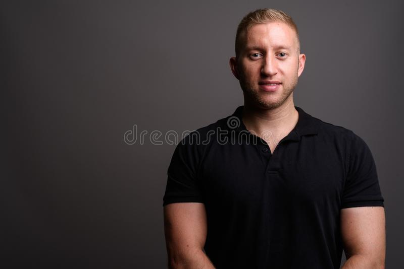 Man with blond hair wearing black polo shirt against gray backgr. Studio shot of man with blond hair wearing black polo shirt against gray background royalty free stock image