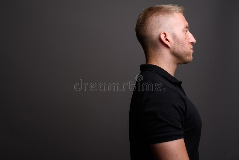 Man with blond hair wearing black polo shirt against gray backgr. Studio shot of man with blond hair wearing black polo shirt against gray background stock photography