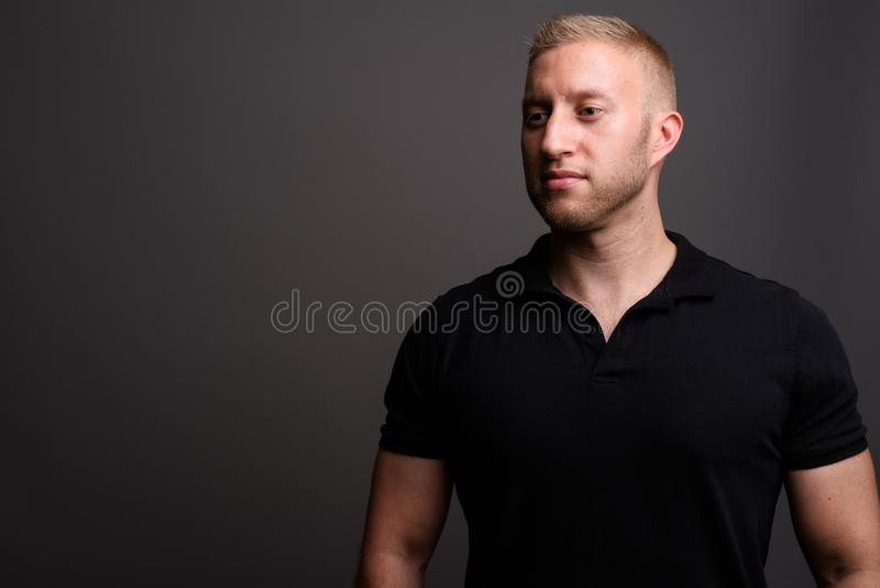 Man with blond hair wearing black polo shirt against gray backgr. Studio shot of man with blond hair wearing black polo shirt against gray background stock images