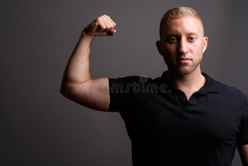 Man with blond hair wearing black polo shirt against gray backgr. Studio shot of man with blond hair wearing black polo shirt against gray background royalty free stock photos