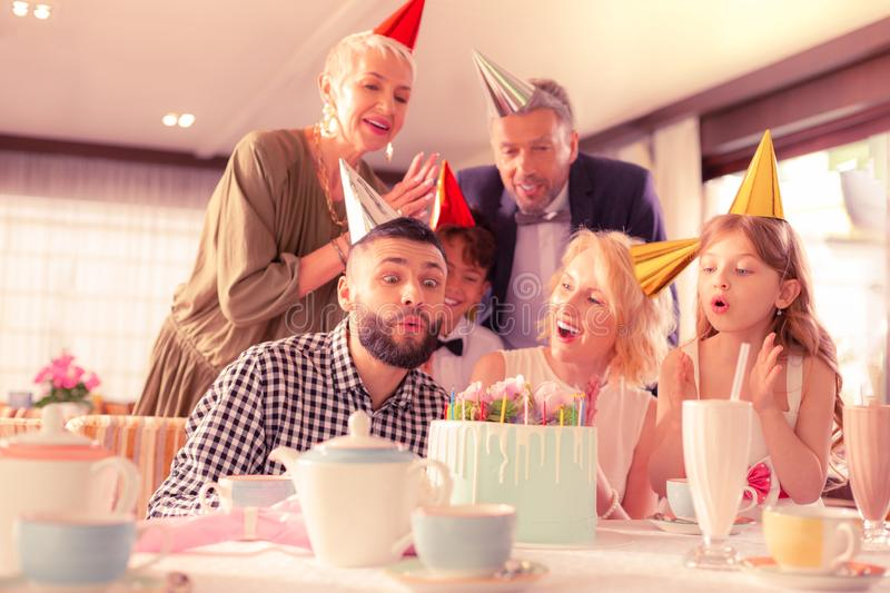 Handsome dark-haired man blowing candles celebrating birthday stock photo