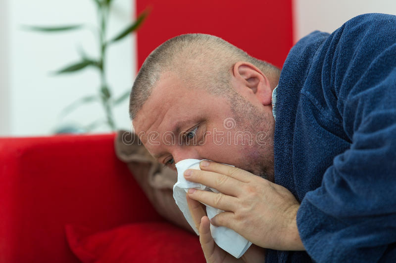 Man blowing his nose in his living room.  stock photography