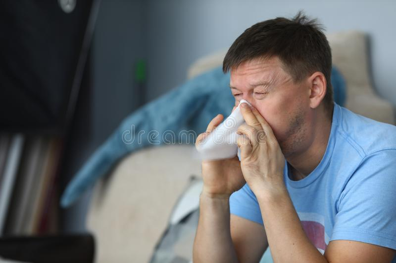 Man blowing his nose in a napkin while sitting. At home on sofa portrait stock photo