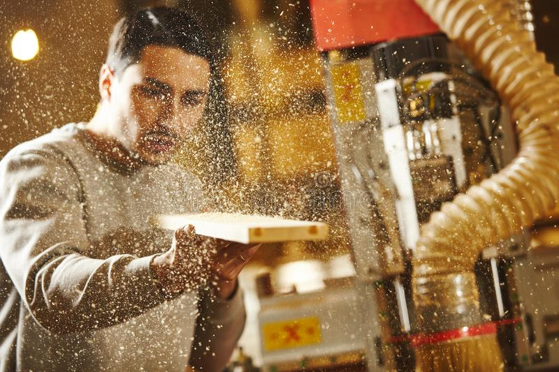 Man blows sawdust off the wood after sanding CNC router machine. Device with numerical control. Woodworking industry royalty free stock photo
