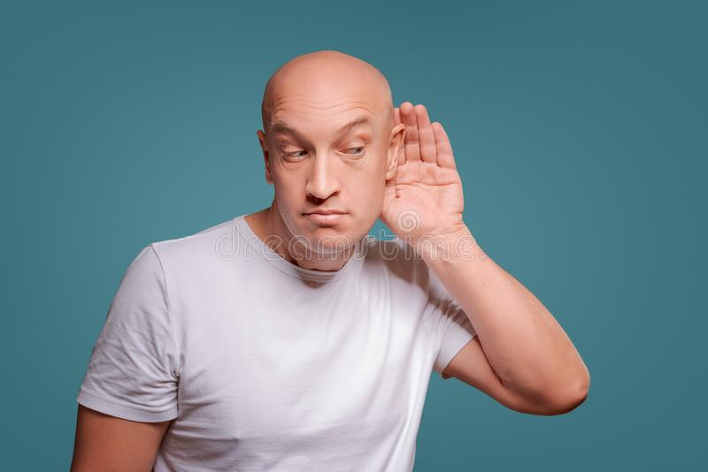 A man on a blue background in holding his hands near his ear, eavesdropping royalty free stock photos