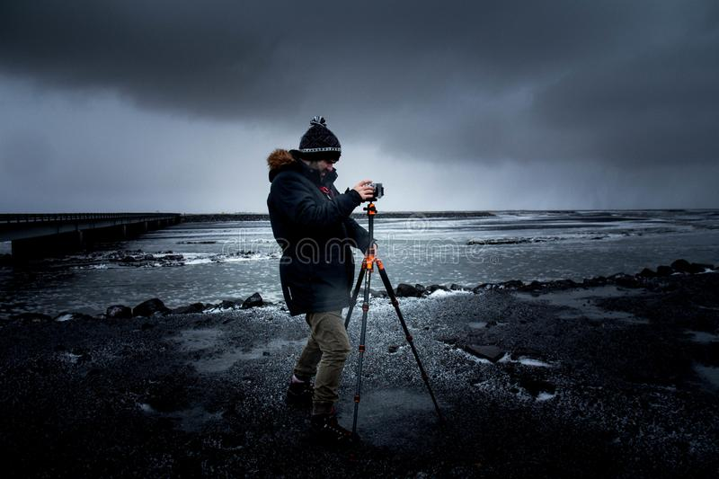Man in Blue Coat Holding a Tripod With Camera stock images
