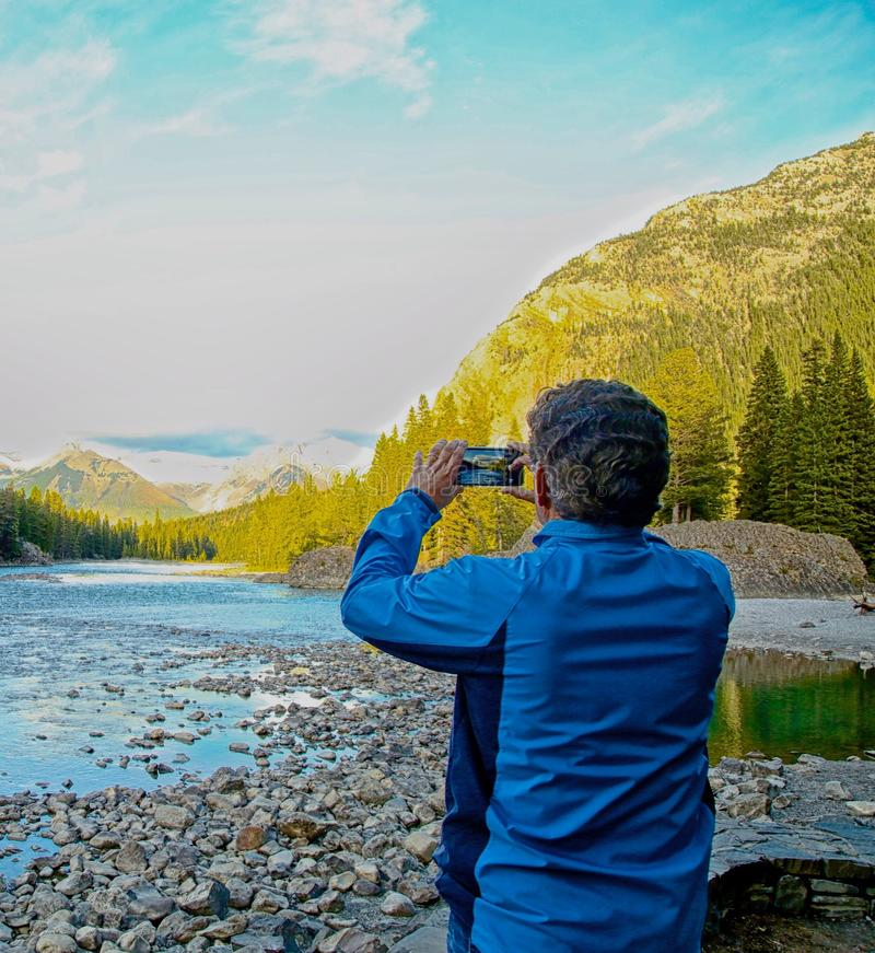 Man taking picture. Man in blue coat taking picture of Bow Lake surrounded by mountains in Banff National Park Alberta royalty free stock image