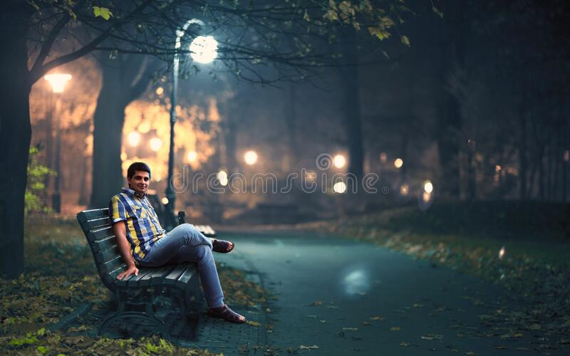 Man in Blue Denim Jeans Sitting Down by Wooden Bench Near Post Lamp Lighted stock photo