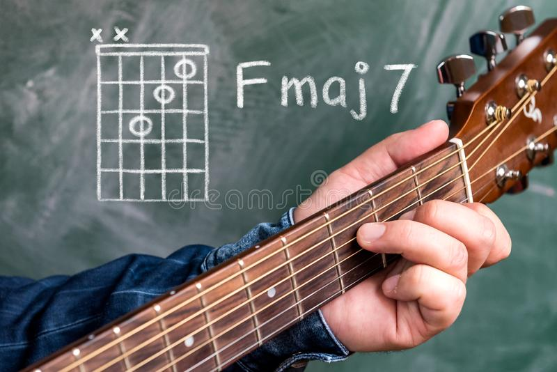 Man playing guitar chords displayed on a blackboard, Chord F major 7 royalty free stock image