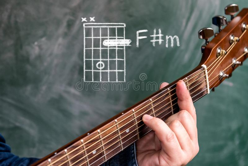 Man playing guitar chords displayed on a blackboard, Chord F sharp minor. Man in a blue denim shirt playing guitar chords displayed on a blackboard, Chord F royalty free stock images