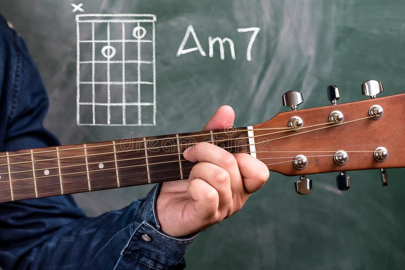 Man Playing Guitar Chords Displayed On A Blackboard Chord Am7 Stock