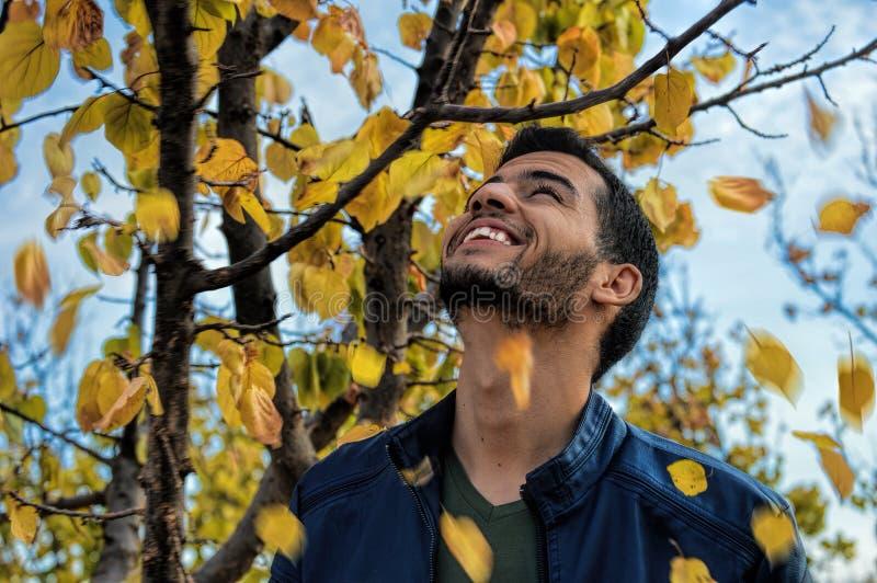 Man With Blue Denim Zip-up Jacket Near Yellow Leaf Tree stock photo