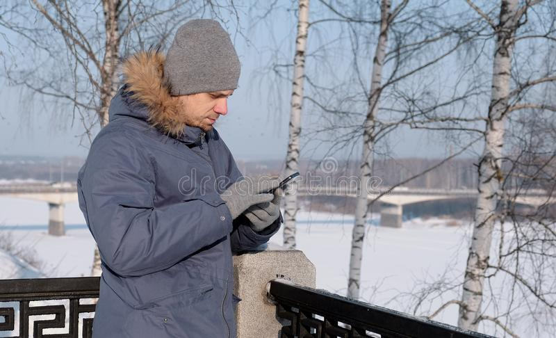 Man in blue down jacket with fur hood using his cellphone for web and chatting in a winter Park. stock image