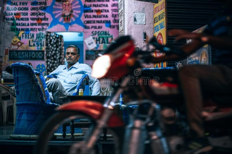 Man in Blue Dress Shirt Sitting on Blue Chair Beside Pink Painted Wall royalty free stock images