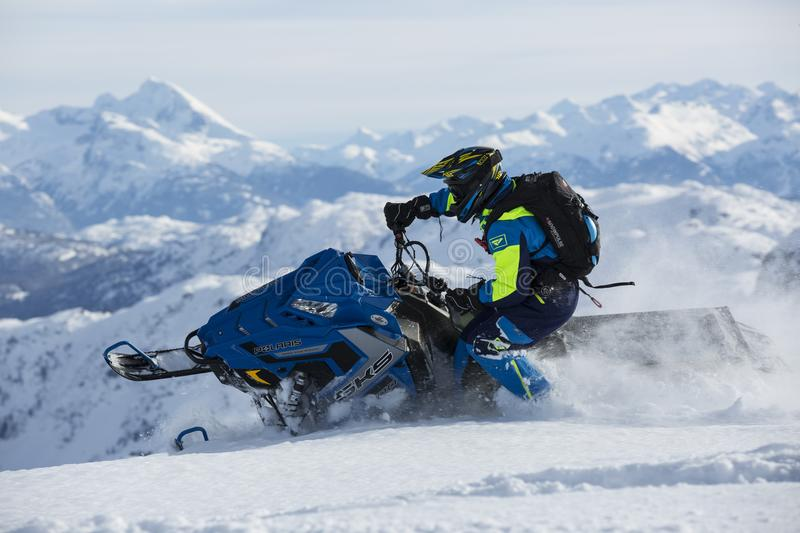 Man In Blue And Green Long-sleeved Suit Riding On Snowmobile royalty free stock photos